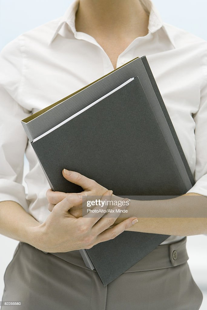 Female professional holding folders, cropped view : Stock Photo