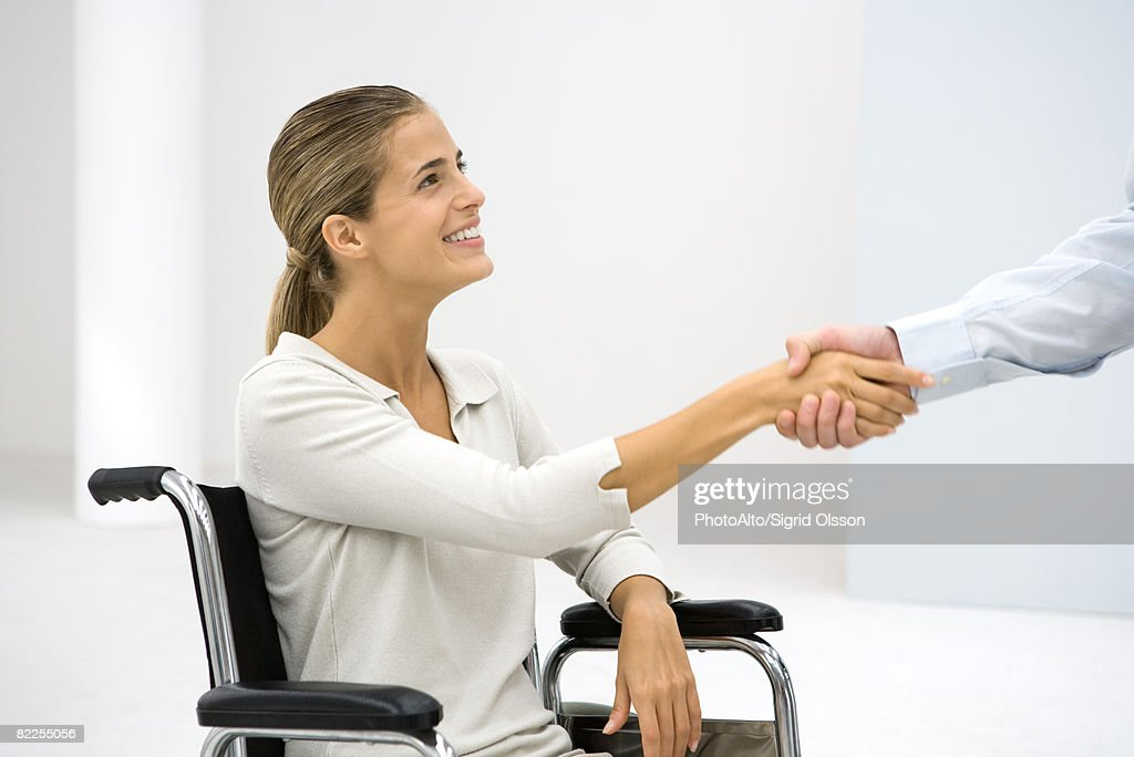 Female professional in wheelchair, shaking man's hand, cropped view : Stock Photo