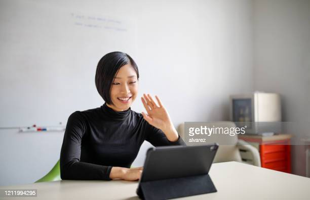 female professional making a video call in office - japanese ethnicity stock pictures, royalty-free photos & images