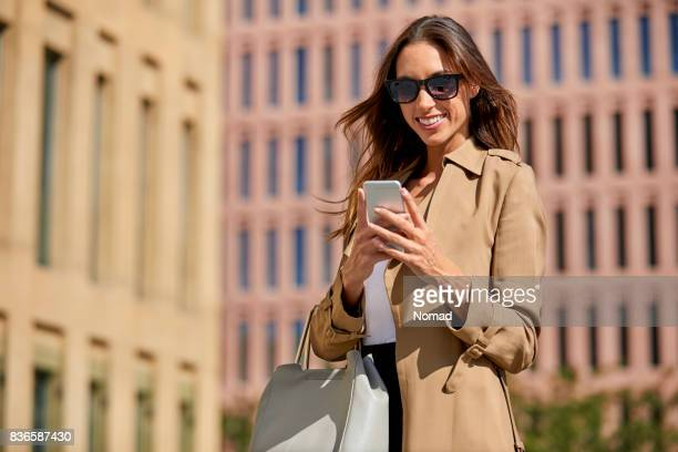 female professional messaging through smart phone - brown purse stock pictures, royalty-free photos & images