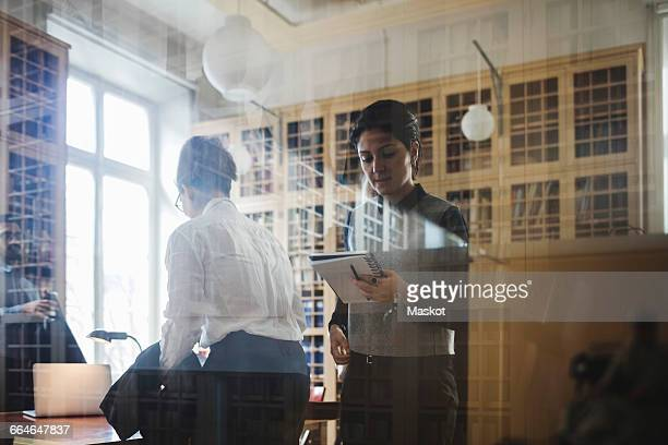 Female professional reading from spiral notebook seen through glass in library