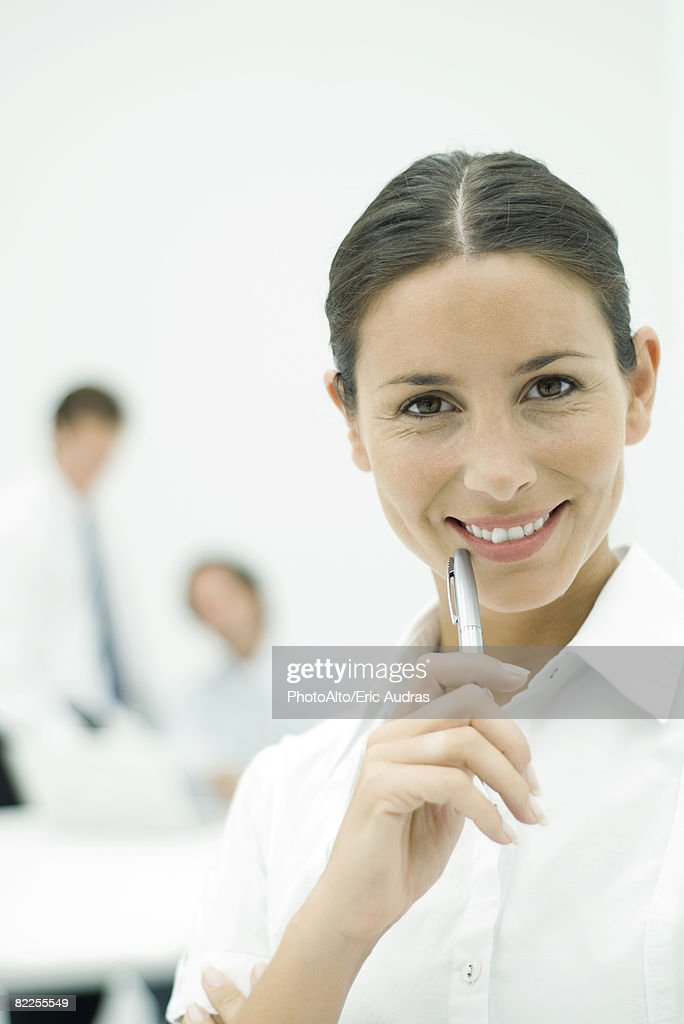 Female professional smiling at camera, holding pen up to chin, portrait : Stock Photo