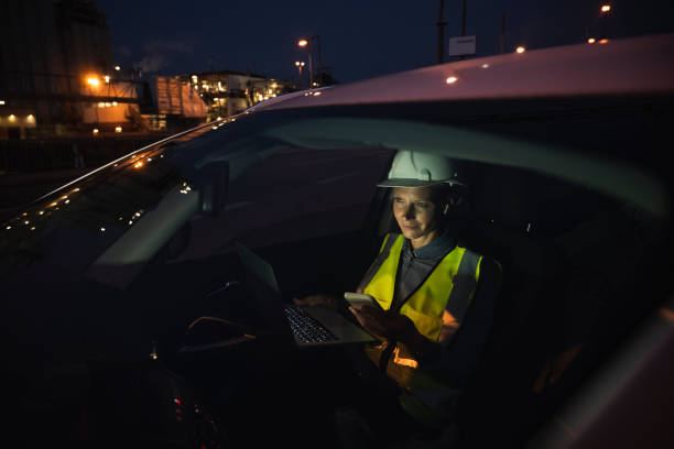 Female professional using technologies while sitting in car seen through windshield at night