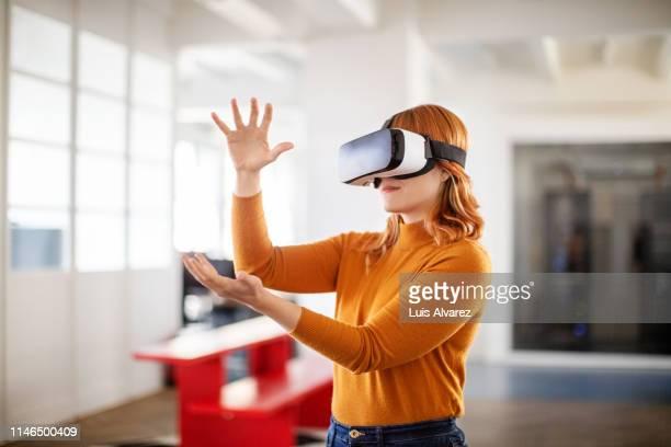female professional using vr glasses in office - naranja color fotografías e imágenes de stock