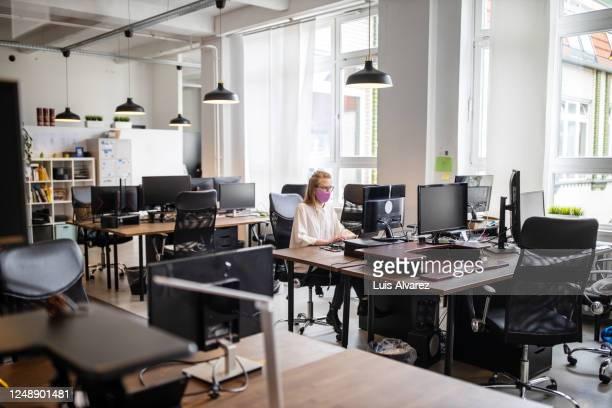 female professional working alone in office - コンセプト ニューノーマル ストックフォトと画像