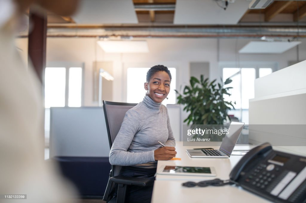 Female professional working at her desk : Stock Photo