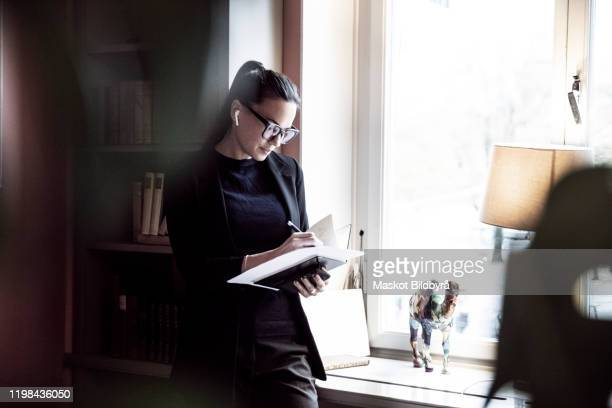 female professional writing on documents while standing by window at law firm - bedrijven financiën en industrie stockfoto's en -beelden