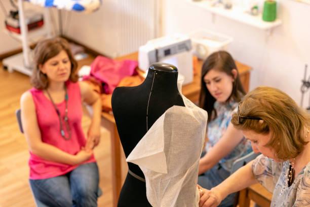 Female professionals looking at senior designer working on mannequin in studio