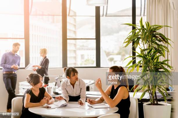 Female professionals planning at table in office