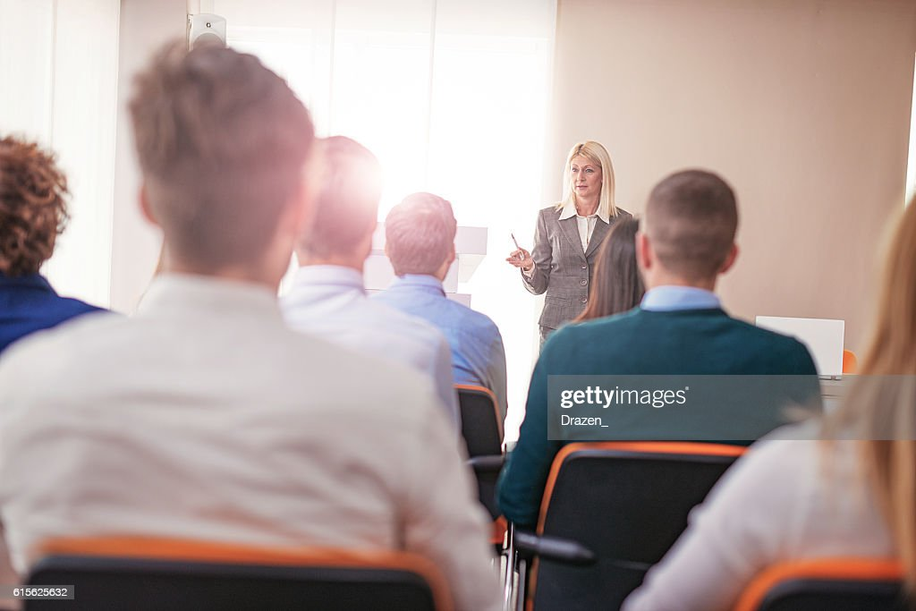 Female professor at faculty class, having discussion with students : Foto de stock