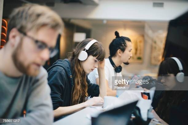 Female programmer working on computer with male colleagues at desk in office