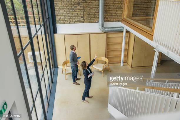 female property agent showing man around empty office space - lease agreement stock pictures, royalty-free photos & images