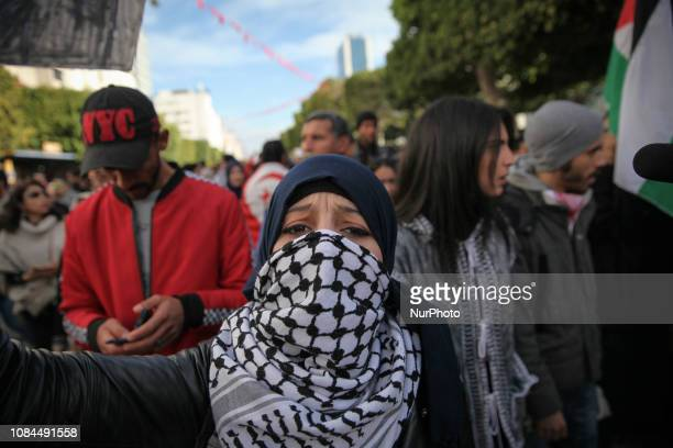 Female protester covering her face with the Palestinian scarf keffiyeh, attends a march held by the Tunisian General Labour Union on Avenue Habib...