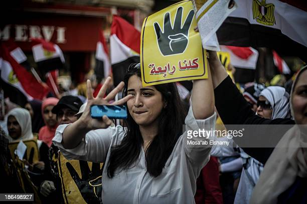 CONTENT] A female protester gestures the symbolic four finger Rabaa sign during anticoup marches in Cairo