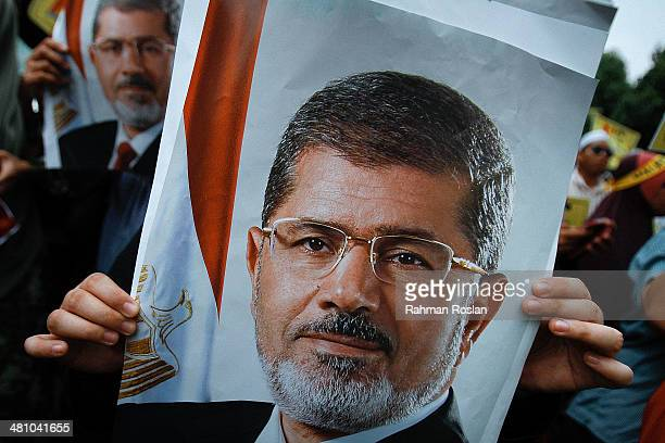 A female protester hold a poster of Mohammed Morsi Egypt's ousted president during a protest against the mass execution sentence of 529 supporters of...