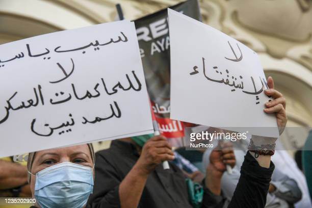 Female protester holds a placard that reads in Arabic release Yassine Ayari, no to the military trials of civilians and another that reads no to the...