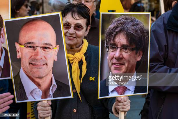 A female protester is seen among the portraits of former President Puigdemont and Councilor Raül Romeva Act of protest to request the release of...
