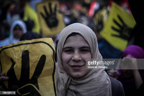 CONTENT] A female protester is seen during anticoup march in Cairo with the symbolic yellow four finger Rabaa sign