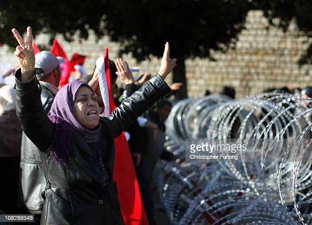 Female protester pleads with soldiers to allow her through the razor wire barricade outside the Tunisian prime minister's office on January 24, 2011...