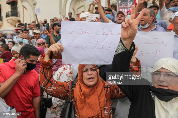 Female protester raises a placard that reads in Arabic, down with the coup, as another protester makes victory sign , during a demonstration held in...