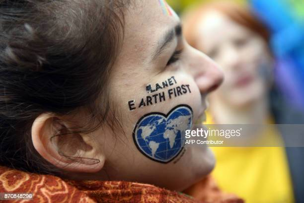 A female protester wears the slogan «Planet Earth First» on her skin at a demonstration of the environmental organization Greenpeace under the motto...
