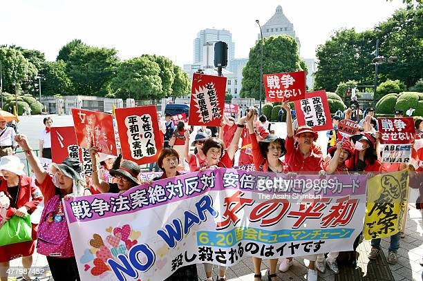 Female protesters march on during a rally in front of the diet building on June 20 2015 in Tokyo Japan Donning red clothing to represent their anger...
