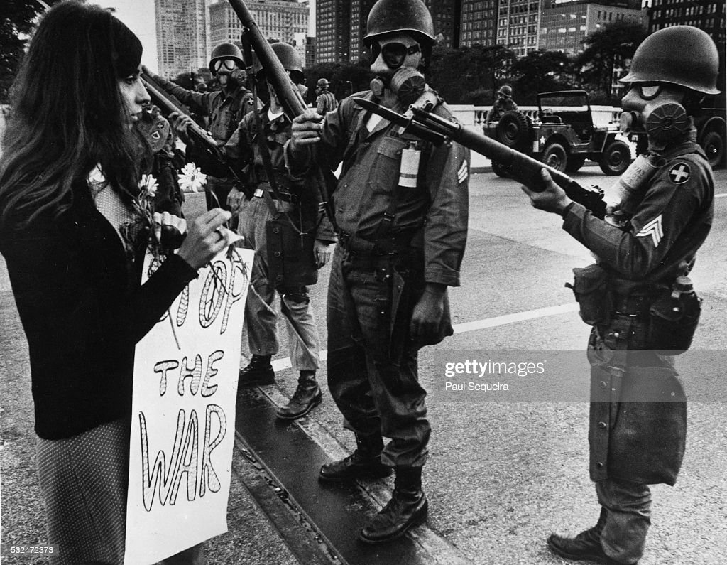 A female protestor, holding a flower and sign that reads 'Stop The War,' approaches soldiers wearing riot gear who are guarding the bridge approach to Michigan Avenue from Grant Park during the Democratic National Convention, Chicago, Illinois, August 28, 1968.