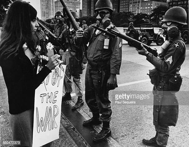 A female protestor holding a flower and sign that reads 'Stop The War' approaches soldiers wearing riot gear who are guarding the bridge approach to...