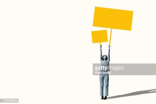 female protestor holding blank yellow placards - placard stock pictures, royalty-free photos & images