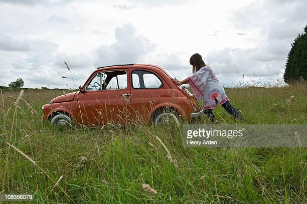 Female pushing car in field