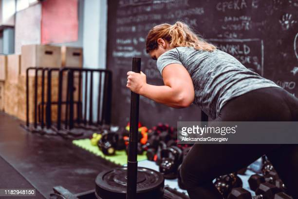 female pushing weight cart in gym - toughness stock pictures, royalty-free photos & images