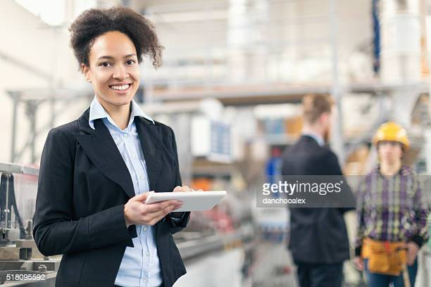 Female quality control inspector using tablet pc in the factory