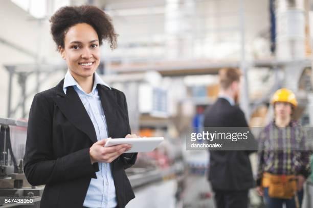 Inspecteur van de vrouwelijke kwaliteit met behulp van tablet pc en lachend voor camera