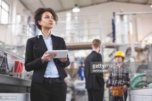 Weibliche Qualitätsprüfer mit Tablet-pc am Werk