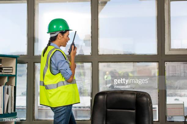 female quarry worker standing in site office talking on radio device - beschützer stock-fotos und bilder