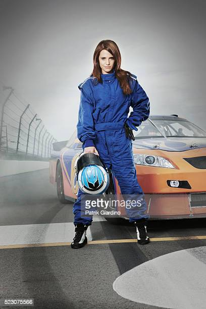 Female race car driver standing in front of racecar