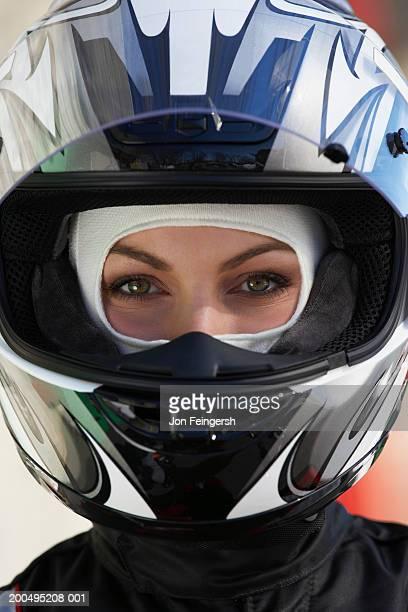 Female race car driver wearing helmet, close-up, portrait