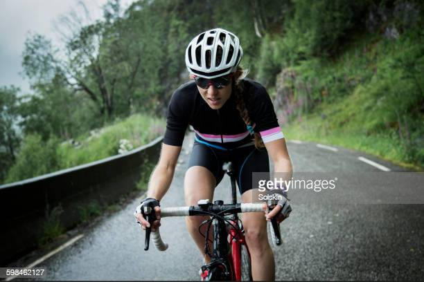 female race cyclist on mountain road - wielrennen stockfoto's en -beelden