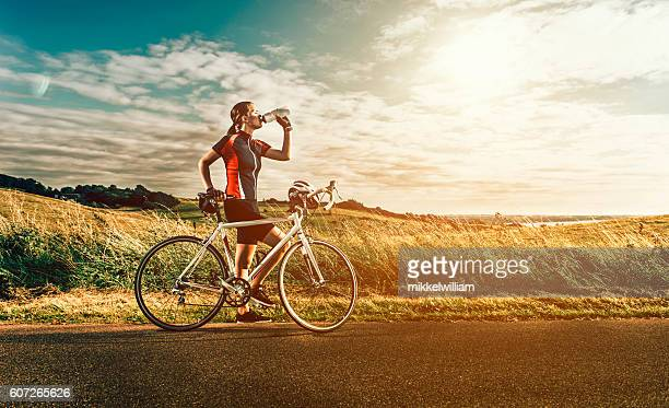female race cyclist stands next to bike near the sea - racing bicycle stock pictures, royalty-free photos & images
