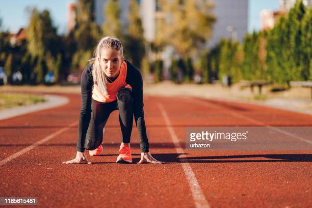 female race runner on a racing track - sports race stock pictures, royalty-free photos & images