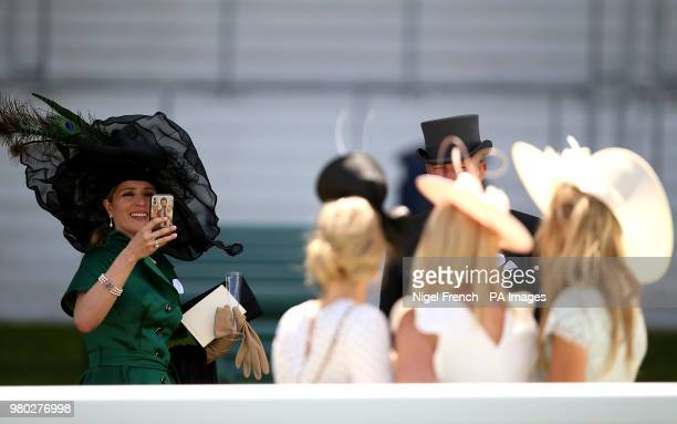 Female racegoer takes a photo of other racegoer during day three of Royal Ascot at Ascot Racecourse.