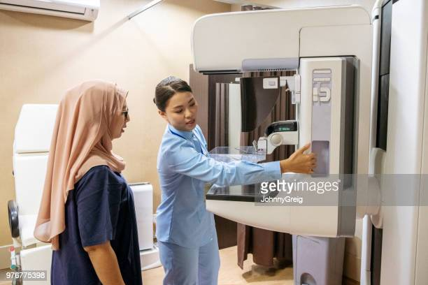 female radiologist setting up mammogram machine - mammogram stock pictures, royalty-free photos & images