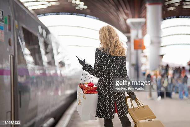 Female rail traveller holding presents and mobile