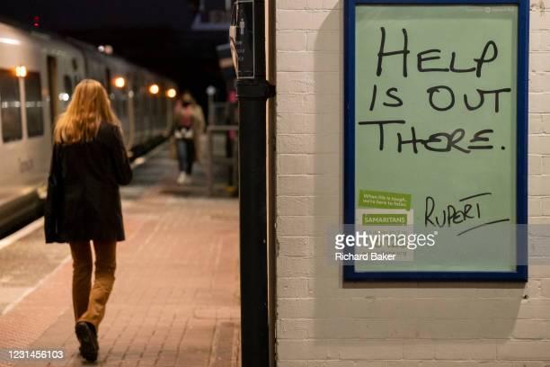 Female rail traveller walks along the platform at Loughborough Junction railway station where a Samaritan's poster urges those with mental health...