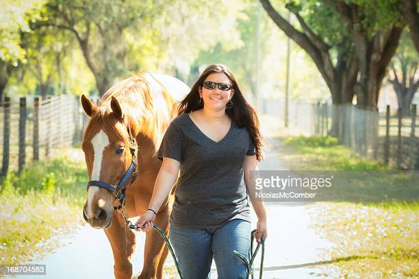 Female Ranch Employee Leading a Horse
