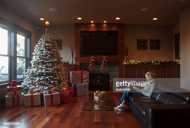 Female Reading a Book in Her Christmas Decorated Living Room