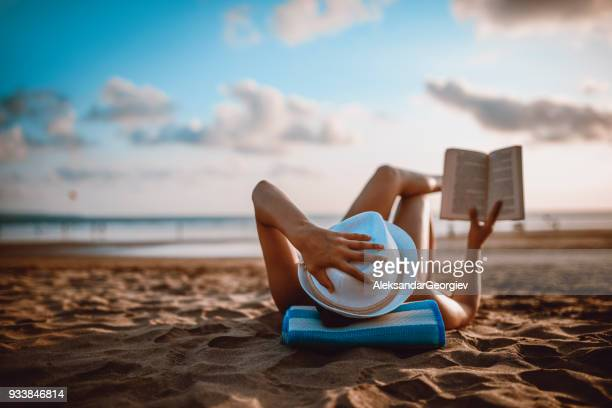 female reading and enjoying sunset on beach by the ocean - reading stock pictures, royalty-free photos & images