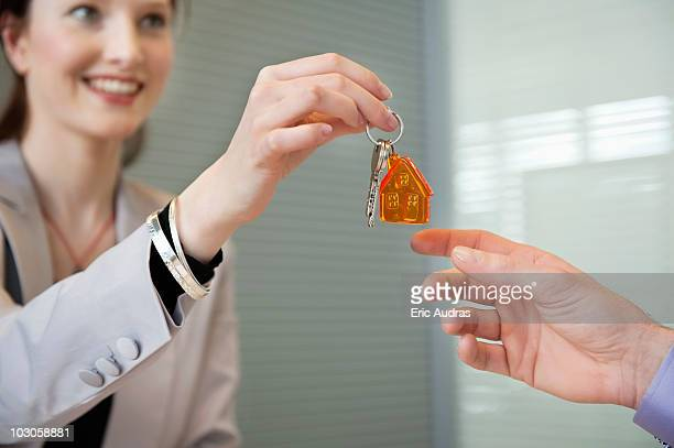 Female real estate agent giving house keys to a man