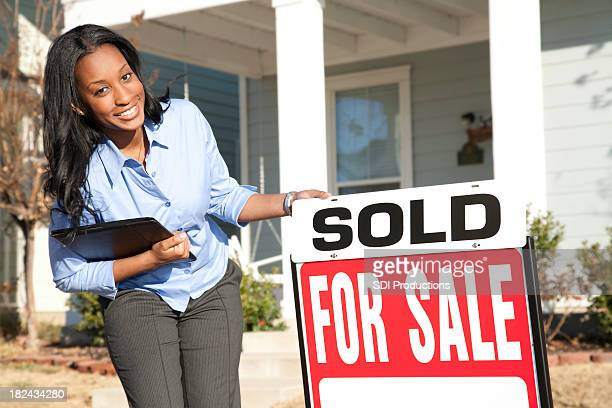 female real estate agent holding sold sign outside home - real estate sign stock pictures, royalty-free photos & images