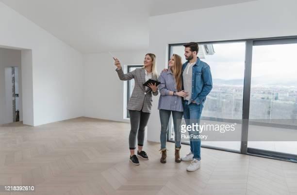若いカップルに販売のためのアパートを示す女性の不動産業者 - 状態 ストックフォトと画像